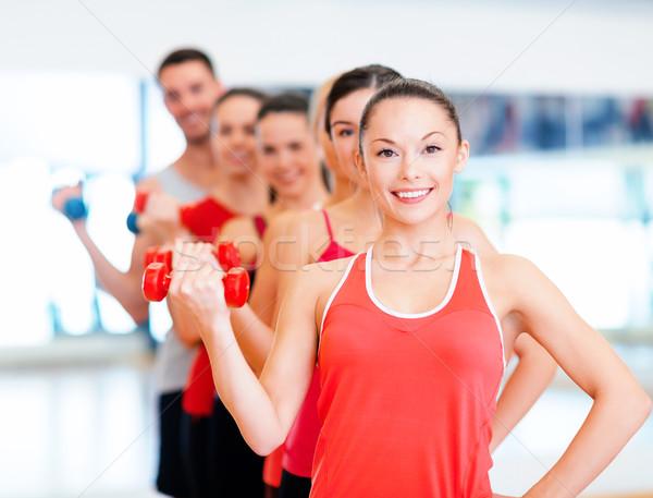 Csoport mosolyog emberek súlyzók tornaterem fitnessz Stock fotó © dolgachov