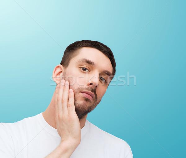 beautiful calm man touching his face Stock photo © dolgachov