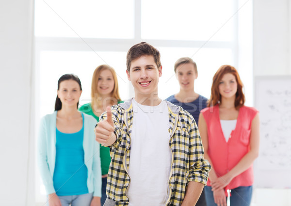 male student with classmates showing thumbs up Stock photo © dolgachov
