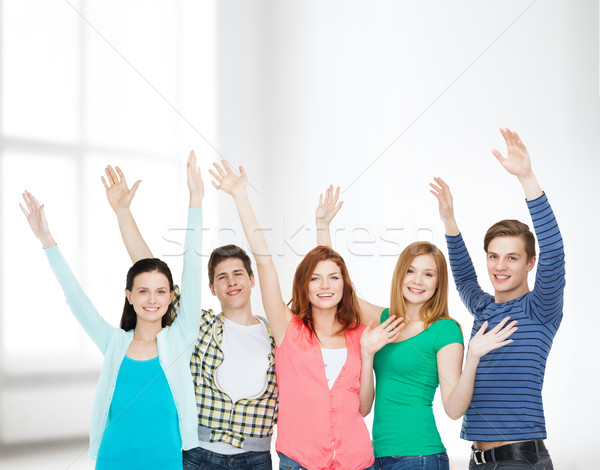group of smiling students waving hands Stock photo © dolgachov
