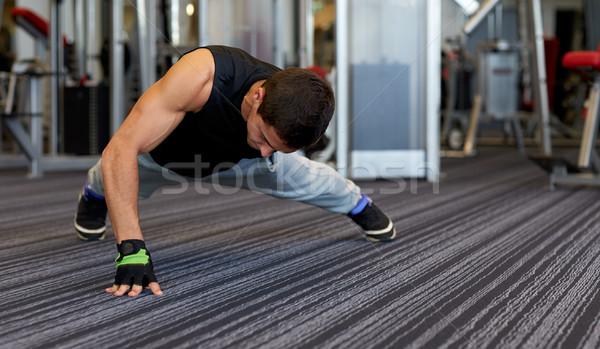man one arm push-ups in gym Stock photo © dolgachov