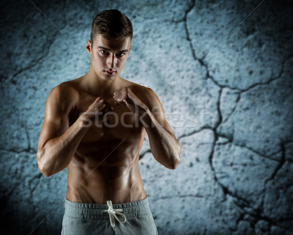 young man in fighting or boxing position Stock photo © dolgachov