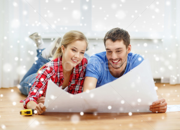 smiling couple with blueprint at home Stock photo © dolgachov