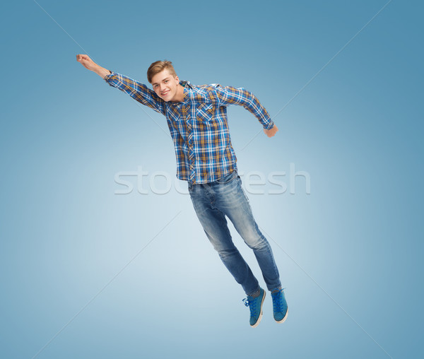 smiling young man jumping in air Stock photo © dolgachov