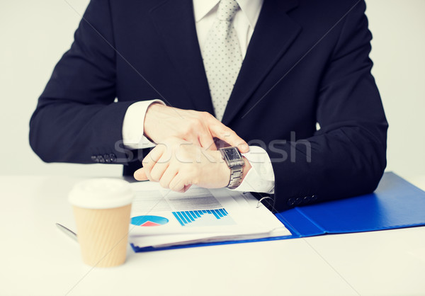 businessman with graphs pointing at watch Stock photo © dolgachov