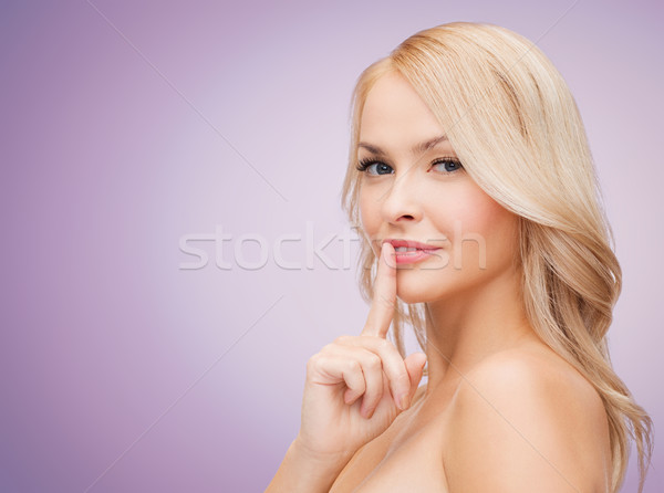 beautiful young woman holding finger on her lips Stock photo © dolgachov