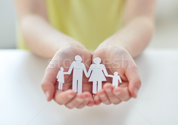 Stock photo: close up of child hands with paper family cutout
