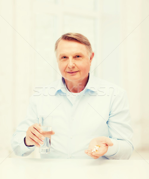 old man with pills ang glass of water Stock photo © dolgachov