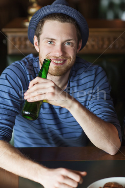 Felice giovane bere birra bar pub Foto d'archivio © dolgachov