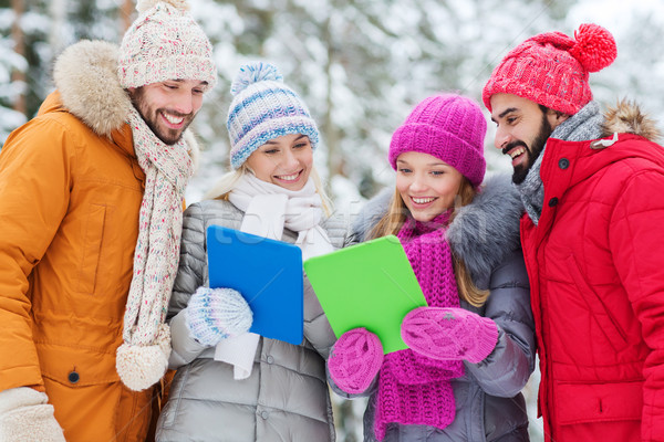 smiling friends with tablet pc in winter forest Stock photo © dolgachov