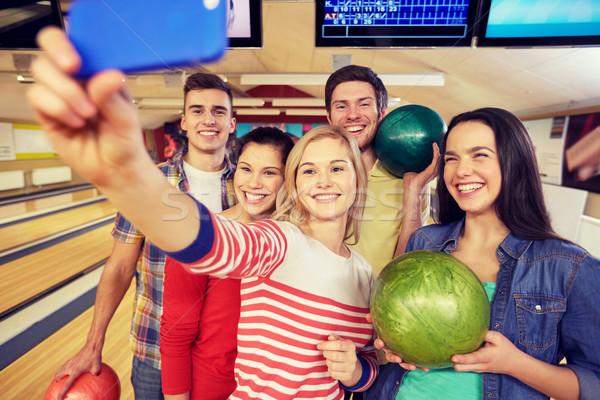 Heureux amis smartphone bowling club personnes Photo stock © dolgachov