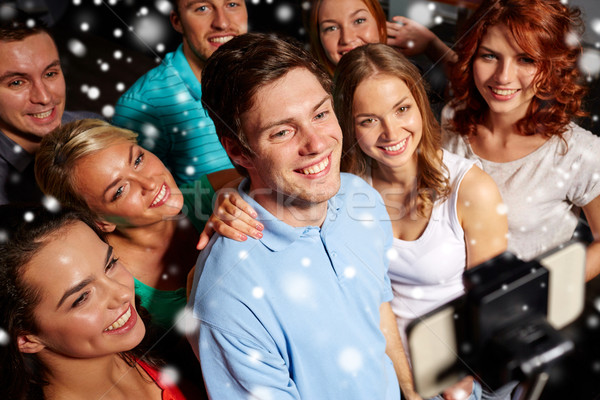 friends with smartphone taking selfie in club Stock photo © dolgachov