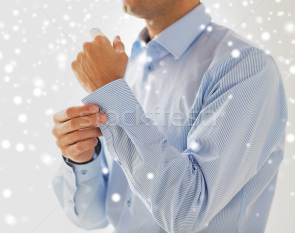 close up of man fastening button on shirt sleeve Stock photo © dolgachov