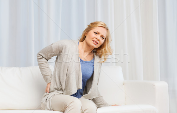 unhappy woman suffering from backache at home Stock photo © dolgachov