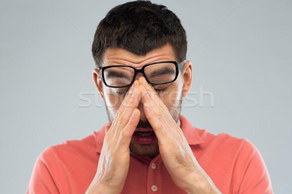 tired man in eyeglasses rubbing eyes Stock photo © dolgachov