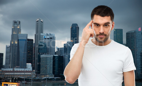 man with finger at temple over singapore city Stock photo © dolgachov