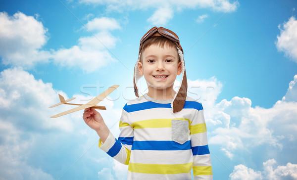 happy little boy in aviator hat with airplane Stock photo © dolgachov