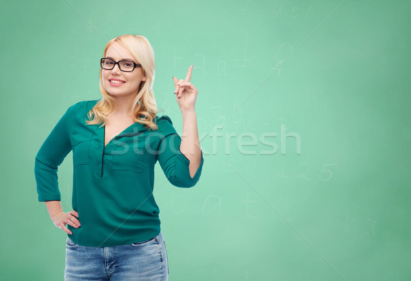 young woman with eyeglasses pointing finger up Stock photo © dolgachov