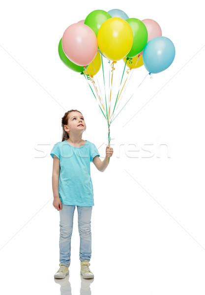 Lány felfelé néz köteg hélium léggömbök gyermekkor Stock fotó © dolgachov