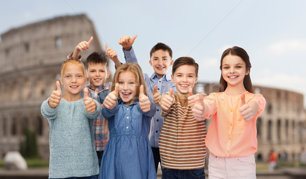 children showing thumbs up over coliseum in rome Stock photo © dolgachov