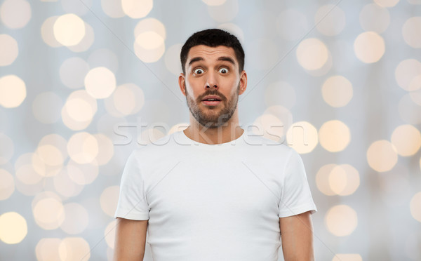 scared man in white t-shirt over lights background Stock photo © dolgachov