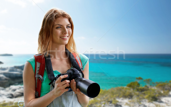 happy woman with backpack and camera over seashore Stock photo © dolgachov