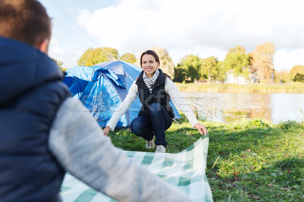 happy couple laying picnic blanket at campsite Stock photo © dolgachov