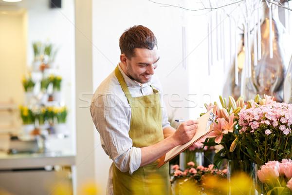 florist man with clipboard at flower shop Stock photo © dolgachov