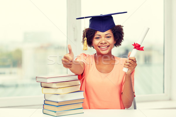 happy african bachelor girl with books and diploma Stock photo © dolgachov