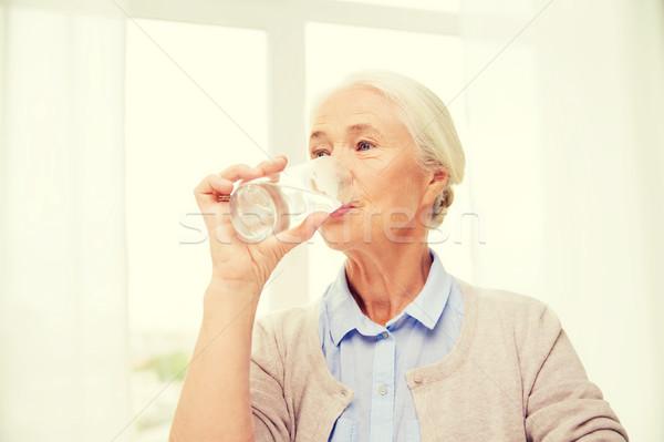 Szczęśliwy starszy kobieta szkła wody domu Zdjęcia stock © dolgachov