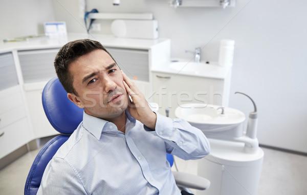 Uomo mal di denti seduta dental sedia persone Foto d'archivio © dolgachov