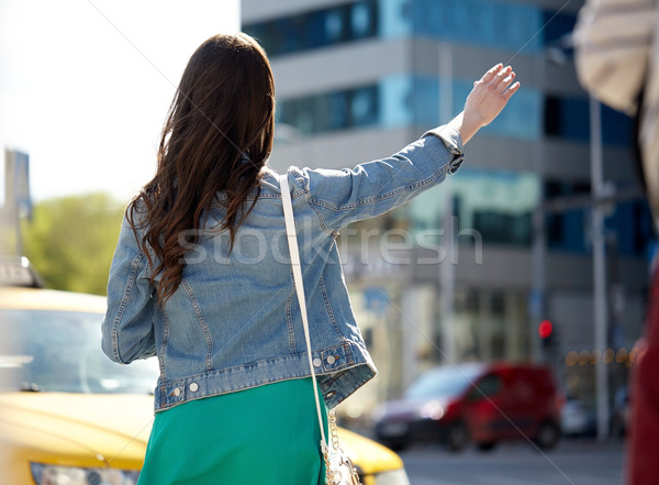 young woman or girl catching taxi on city street Stock photo © dolgachov
