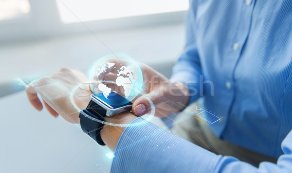 Stock photo: close up of hands and globe hologram on smartwatch