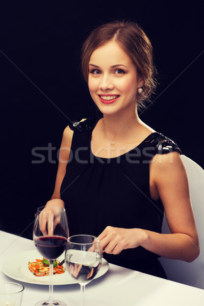 Sorridente mulher jovem alimentação restaurante pessoas Foto stock © dolgachov