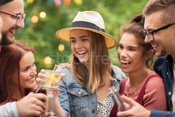 happy friends clinking glasses at summer garden Stock photo © dolgachov
