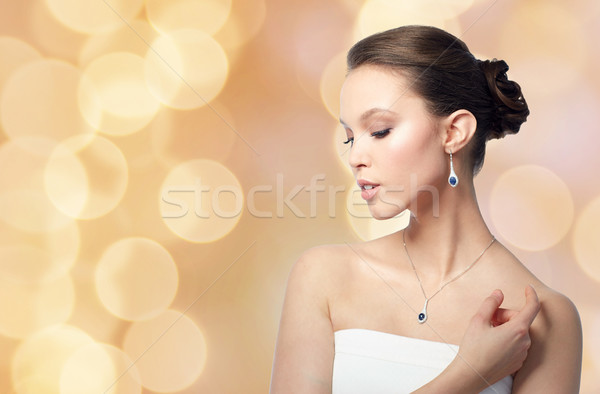 beautiful woman with jewelry over holidays lights Stock photo © dolgachov