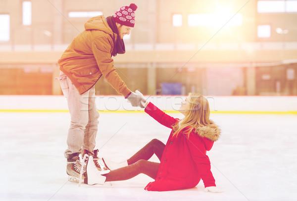 Férfi segít nők felfelé korcsolyázás pálya Stock fotó © dolgachov