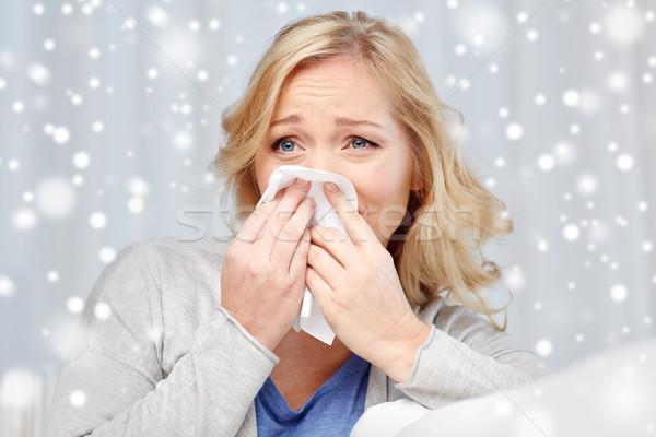 ill woman blowing nose to paper napkin Stock photo © dolgachov