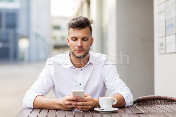 man with smartphone and coffee at city cafe Stock photo © dolgachov
