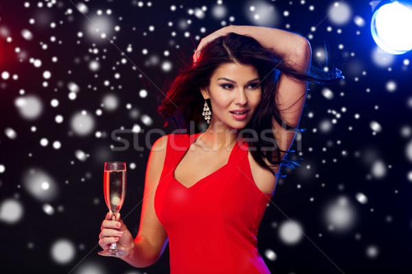 beautiful woman with champagne glass at nightclub Stock photo © dolgachov