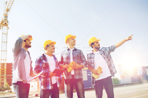 group of smiling builders with tablet pc outdoors Stock photo © dolgachov