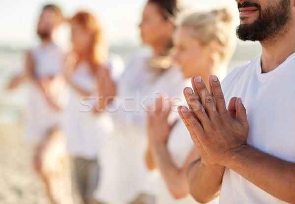Csoportkép készít jóga meditál tengerpart fitnessz Stock fotó © dolgachov