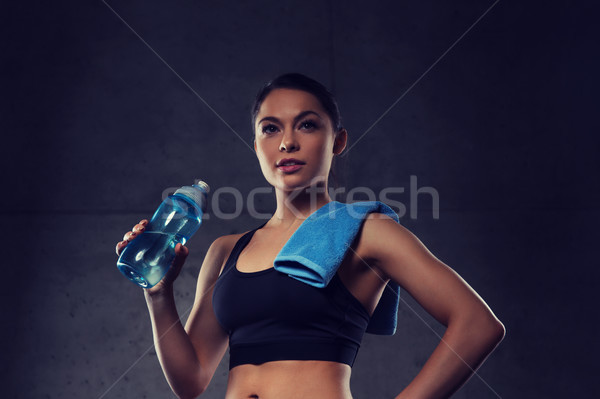 woman with towel drinking water from bottle in gym Stock photo © dolgachov