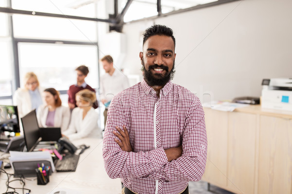 happy indian man over creative team in office Stock photo © dolgachov