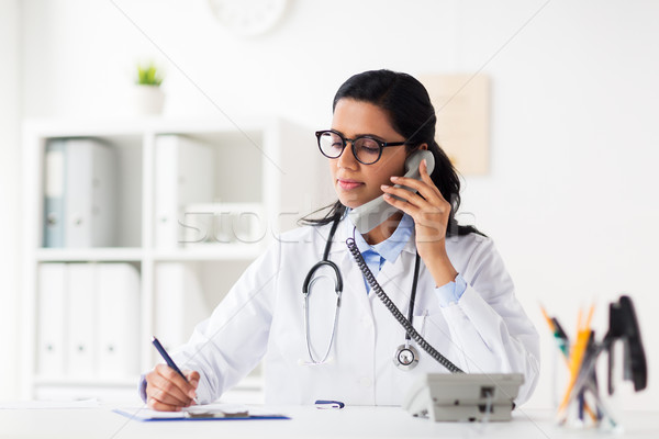 doctor with clipboard calling on phone at hospital Stock photo © dolgachov