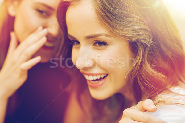 smiling young women gossiping and whispering Stock photo © dolgachov