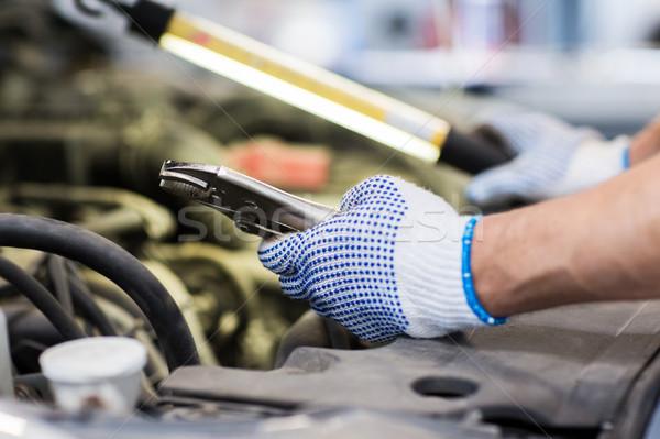 mechanic man with pliers repairing car at workshop Stock photo © dolgachov