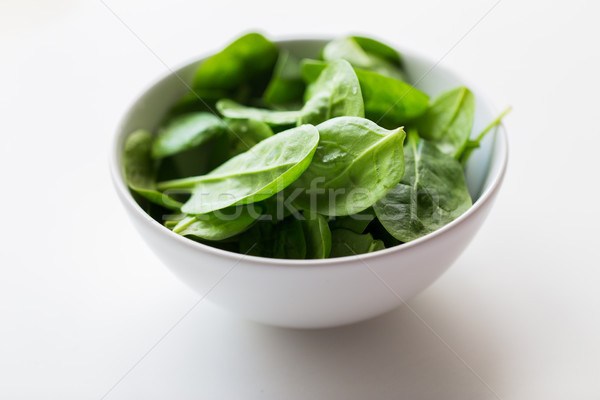 close up of spinach leaves in white bowl Stock photo © dolgachov