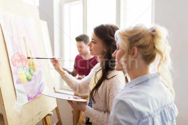 artists with palette and easel at art school Stock photo © dolgachov