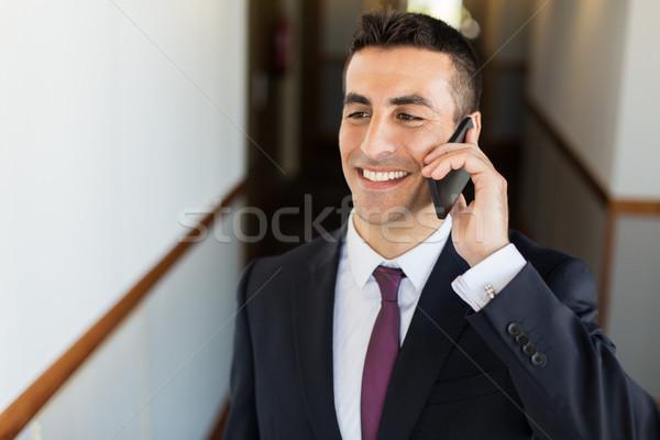 smiling businessman calling on smartphone at hotel Stock photo © dolgachov